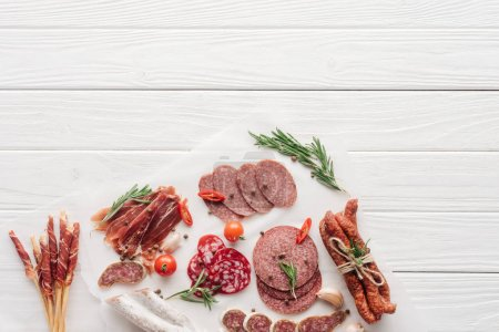 Photo for Top view of arrangement of various meat snacks and rosemary on white wooden backdrop - Royalty Free Image