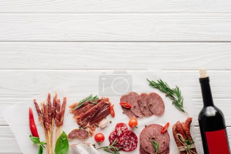 flat lay with meat snacks and bottle of red wine on white wooden background