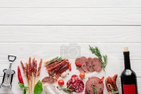 flat lay with bottle of red wine, bottle opener and meat snacks on wooden surface