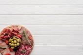 """Постер, картина, фотообои """"вид сверху расположение различных мясных закусок и оливки на белом фоне деревянные"""""""