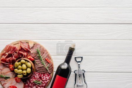 Photo for Flat lay with bottle of red wine, bottle opener and meat snacks on wooden surface - Royalty Free Image