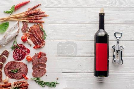 Photo pour Pose plate avec bouteille de vin rouge, ouvre-bouteille et collations à la viande sur la surface en bois - image libre de droit