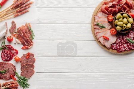 top view of arrangement of various meat snacks and olives on white wooden backdrop