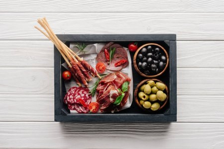 top view of meat appetizers, basil leaves, rosemary and olives in wooden box on white wooden backdrop