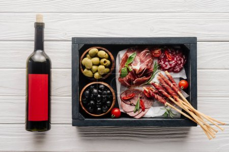 Photo for Top view of bottle of red wine and assorted meat snacks on white wooden tabletop - Royalty Free Image