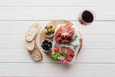 flat lay with meat appetizers, pieces of bread and glass of red wine on white wooden backdrop