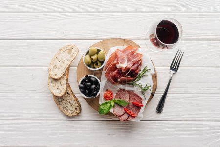 Photo for Flat lay with meat appetizers, pieces of bread and glass of red wine on white wooden backdrop - Royalty Free Image