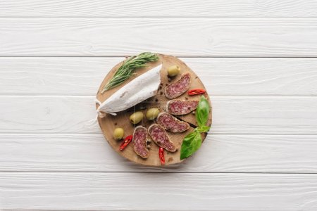 Photo for Top view of meat appetizers with olives, rosemary and basil leaves on white wooden tabletop - Royalty Free Image