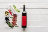 """Постер, картина, фотообои """"вид сверху бутылка красного вина и ассорти из мясных закусок на белые деревянные настольные"""""""