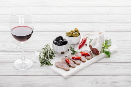 close up view of glass of red wine, olives and assorted meat snacks on white wooden tabletop