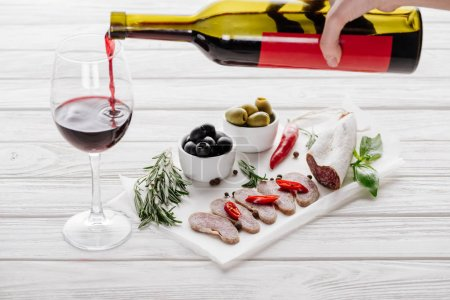 partial view of woman pouring red wine into glass on white wooden tabletop with meat appetizers near by
