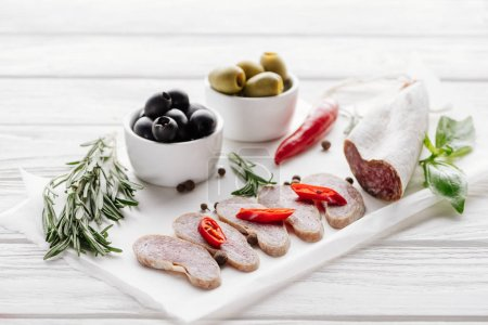 Photo for Close up view of meat appetizers with olives, rosemary and basil leaves on white wooden tabletop - Royalty Free Image