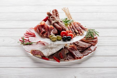 Photo for Close up view of delicious meat appetizers with olives and rosemary on white wooden tabletop - Royalty Free Image