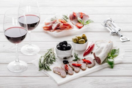 close up view of tasty meat appetizers and glasses of red wine on white wooden surface