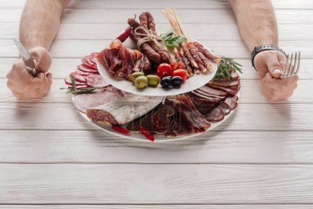 Photo for Partial view of man with cutlery at white wooden tabletop with various meat snacks - Royalty Free Image