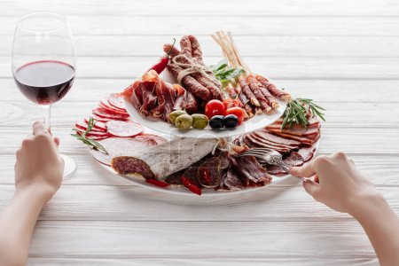 cropped shot of woman, glass of red wine and meat snacks on white wooden surface