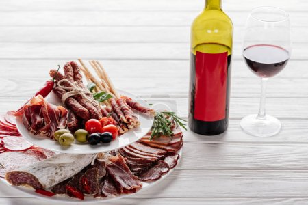 close up view of bottle and glass of red wine and various meat appetisers with olives on white wooden tabletop