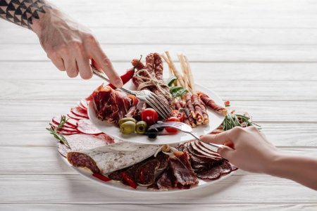 cropped shot of couple trying meat appetizers at white wooden background