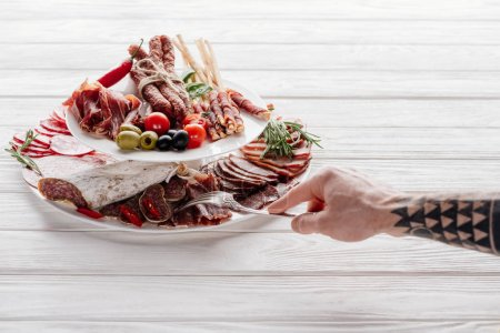 partial view of man trying meat snacks at white wooden tabletop