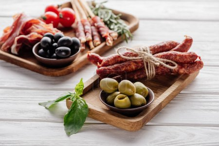 food composition with various meat appetizers, olives and basil leaves on white wooden surface