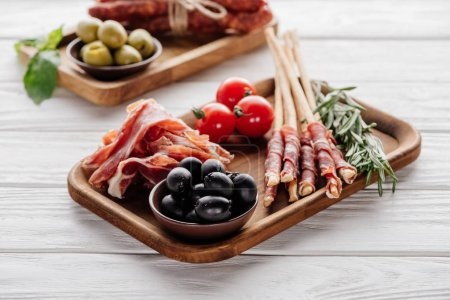 food composition with various meat appetizers, olives and rosemary on white wooden surface