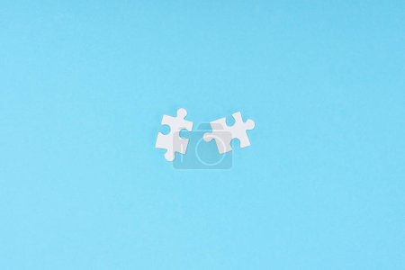 Photo for Top view of white puzzle pieces arranged on blue backdrop - Royalty Free Image