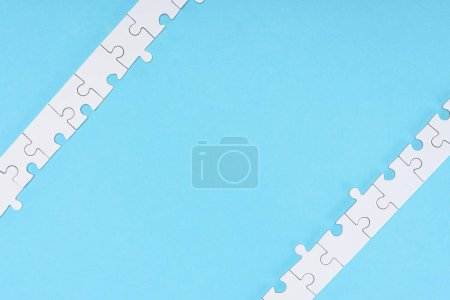top view of white puzzle pieces arranged on blue backdrop