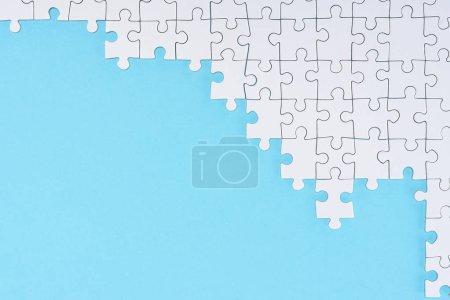 flache Lage mit weißen Puzzleteilen auf blauem Hintergrund