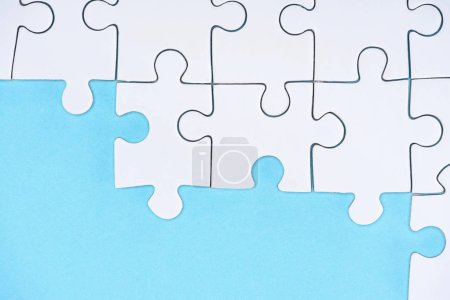 Photo for Top view of white puzzles arrangement on blue background - Royalty Free Image