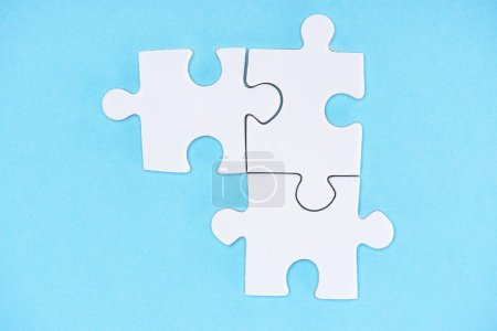 top view of arranged white puzzle elements on blue backdrop