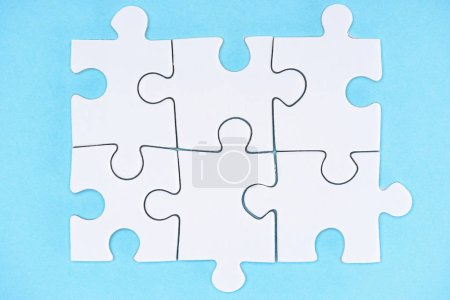 Photo for Top view of arranged white puzzle elements on blue backdrop - Royalty Free Image
