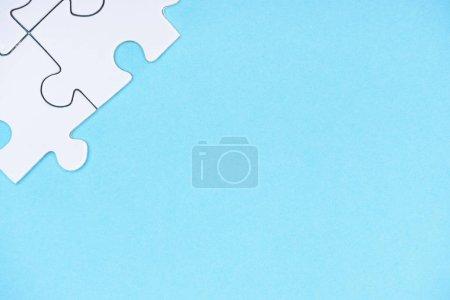 Draufsicht auf weiße Puzzleteile isoliert auf blau