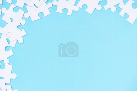 full frame of white puzzles arrangement on blue backdrop