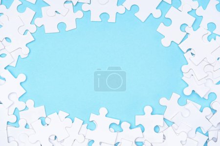 Photo for Full frame of white puzzles arrangement on blue backdrop - Royalty Free Image