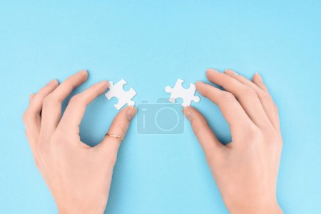 partial view of woman holding white puzzles pieces on blue background