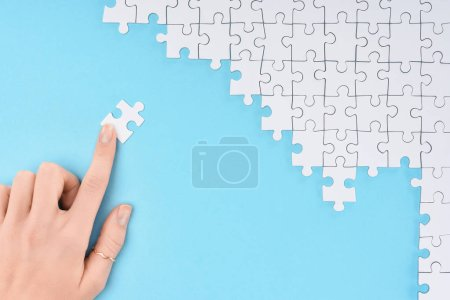 cropped shot of woman and white puzzles pieces on blue background
