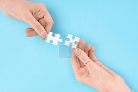 cropped shot of women holding white puzzles in hands on blue backdrop, business cooperation and teamwork concept
