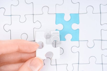 cropped shot of woman with white puzzles pieces on blue background