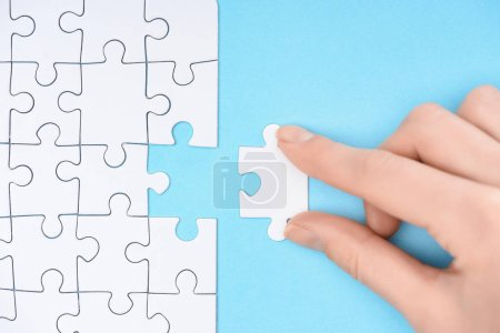 Photo for Partial view of woman with white puzzles pieces on blue background - Royalty Free Image