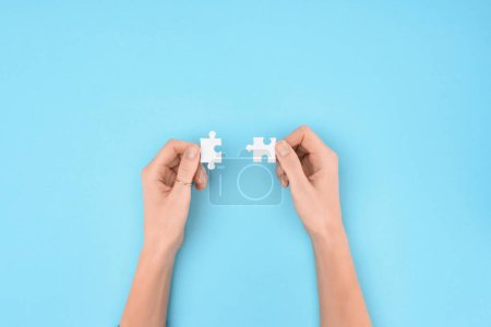 cropped shot of woman holding white puzzles pieces on blue background