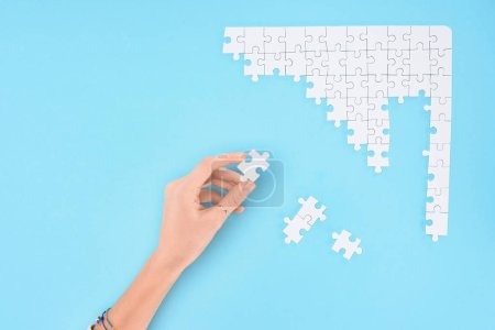 Photo for Cropped shot of woman holding white puzzles piece on blue background - Royalty Free Image