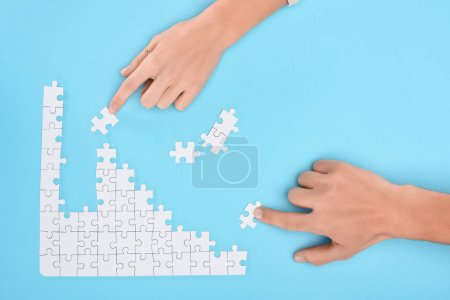 cropped shot of man and woman with white puzzle pieces on blue backdrop, cooperation concept