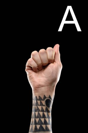 tattooed male hand showing latin letter - A, sign language, isolated on black