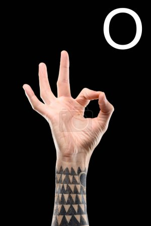Photo for Partial view of tattooed male hand showing cyrillic letter, deaf and dumb language, isolated on black - Royalty Free Image