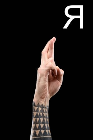 partial view of male tattooed hand showing cyrillic letter, deaf and dumb language, isolated on black