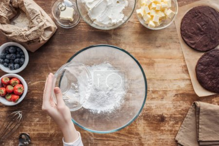 Photo for Partial top view of woman sifting flour and preparing dough for delicious homemade cake - Royalty Free Image