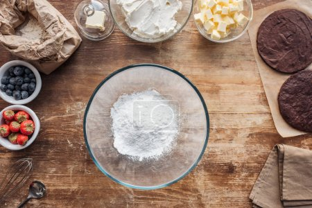 Photo for Top view of bowl with flour and ingredients for sweet homemade cake on table - Royalty Free Image