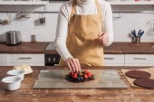 partial view of woman in apron preparing delicious cake with berries in kitchen