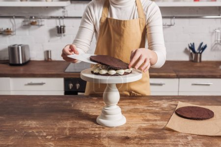 Photo for Mid section of woman in apron preparing gourmet sweet cake in kitchen - Royalty Free Image