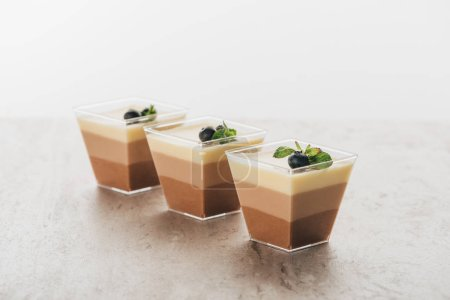 Photo for Delicious triple chocolate mousse desserts in glasses - Royalty Free Image